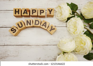 happy sunday word alphabet letters on wooden top view with peony flower decoration