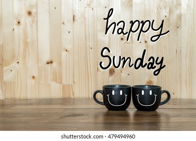 Happy sunday word.Two black cups of coffee and stand together to be heart shape on yellow background with smile face on cup.