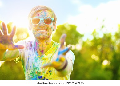 Happy sunny beautiful man male teenager celebrating holi festival in spring, summer day outdoor in green park with light leaks and colorful powder. International spring happy holi holiday concept