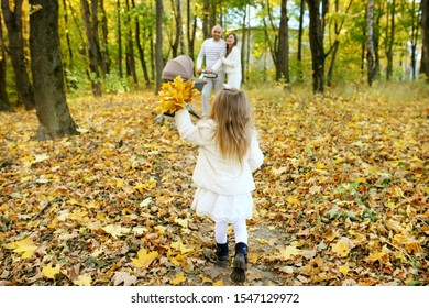 Happy sunny day in autumn park family parents throw yellow leaves over baby and daughter