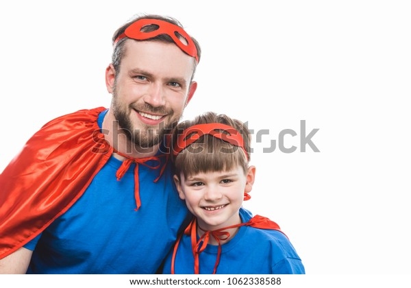 happy super dad and son smiling at camera isolated on white
