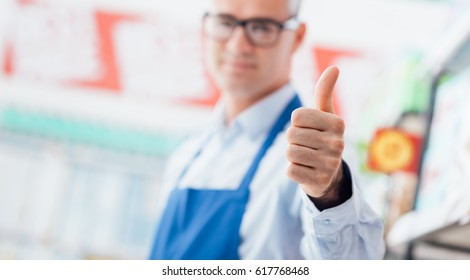 Happy supermarket clerk smiling and giving a thumbs up, he is smiling at camera