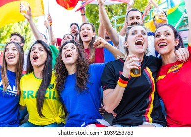 Happy supporters from different countries together at stadium. Women fans from France, Germany, Spain, Brazil and other Italy enjoying a match together. Sport, respect and fair play concepts