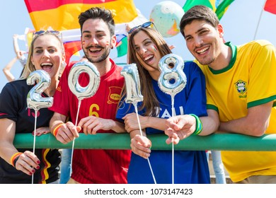 Happy supporters from different countries together at stadium holding a 2018 sign made with balloons. Fans from Italy, Germany, Spain, Brazil and other countries enjoying a match together.