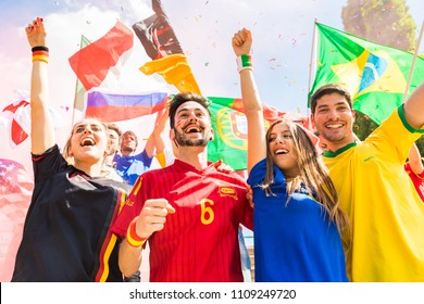 Happy supporters from different countries together at stadium. Fans from France, Germany, Spain, Brazil and other countries enjoying a match together. Sport, achievement and success concepts