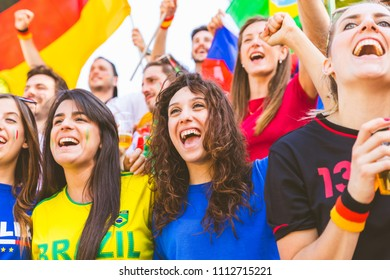 Happy supporters from different countries together at stadium. Girls fans from Germany, Spain, Brazil, Italy and other countries enjoying a match together. Sport, achievement and success concepts