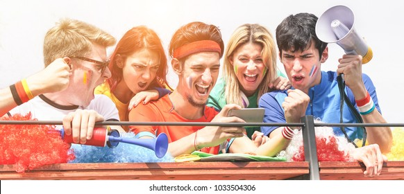 Happy supporters from different countries watching football on smartphone with online sport subscription - Main focus on center man - Crazy fan celebrating a goal in world soccer game - Fun concept