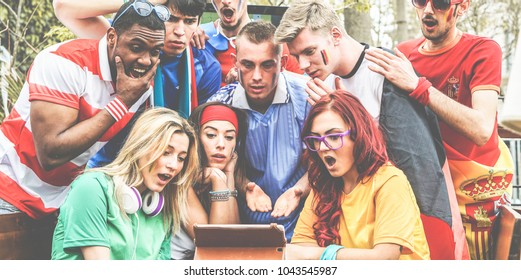 Happy supporters from different countries watching football sport on notepad tablet computer - Main focus on center guys - Multiracial fans are shocked looking world soccer game - Sport concept