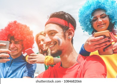 Happy supporters from different countries watching football on smartphones online sport app - Focus on right man face - Crazy fan enjoying world soccer game - Fun and soccer event concept