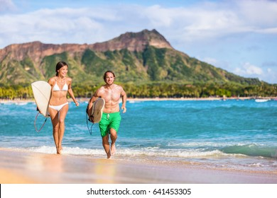 Happy surf people having fun surfing on Waikiki beach, Honolulu, Oahu, Hawaii. Asian woman, caucasian man multiracial couple running out of ocean splashing water.