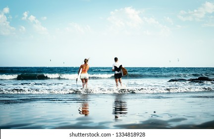 Happy surfer couple going to surf - Sporty people having fun surfing in the ocean - Extreme sport and youth lifestyle concept