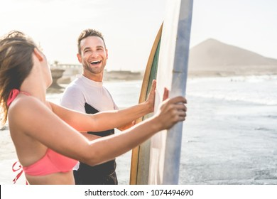 Happy surfer couple laughing with surf boards on the beach - Friends having fun doing extreme sport in vacation - Relationship, and healthy lifestyle concept - Focus on man face