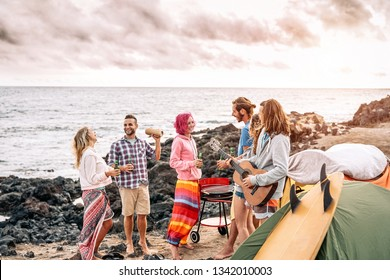 Happy surfer friends making party at sunset while camping next the beach - Young people having fun and drinking beer outdoor - Millennial, summer, vacation and youth holidays lifestyle concept