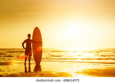 Happy surfer  standing with surfboards on the beach, at sunset.