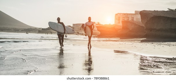 Happy surfers couple running with surf boards on the beach - Sporty people having fun in surfing day - Extreme sport and vacation concept - Main focus on man body and board