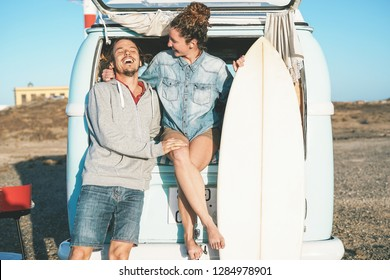Happy surfers couple standing behind on vintage camper mini van - Young people adventuring on road trip with a minivan transport - Concept of travel, vacation, relationship and youth lifestyle
