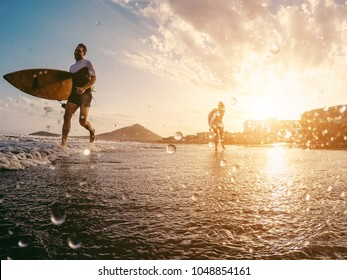 Happy surfers running with surf boards on the beach - Sporty people having fun in sunny day - Extreme sport, travel and vacation concept - Focus on right female silhouette