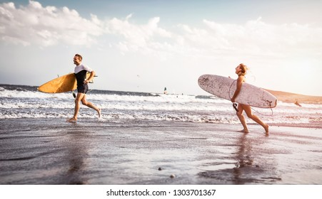 Happy surfers running with surfboards along the sea shore - Sporty couple having fun going to surf together at sunset - Extreme surfing sport, sportive people and youth relationship lifestyle concept