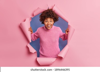Happy surprised Afro American woman stares at camera sees something amazing wears knitted sweater smiles broadly wears casual sweater breaks through paper background. Positive emotions concept