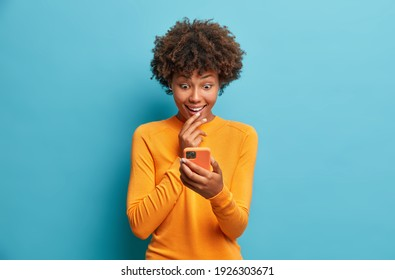 Happy surprised Afro American woman browses internet and networking in social media tests new application for smartphone wears casual jumper isolated over blue background. Mobile communication