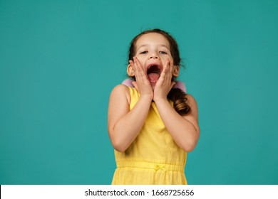 happy surprised beautiful little child girl in dress looking to camera on blue background. Human emotions and facial expression