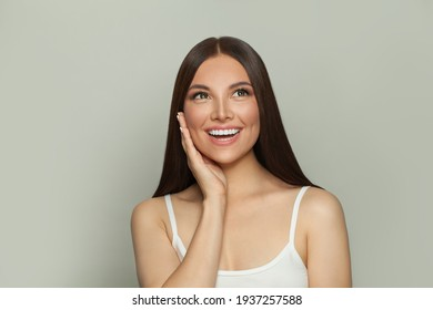 Happy surprised brunette model woman with clear skin and long healthy straight hair on white. Skincare and facial treatment concept