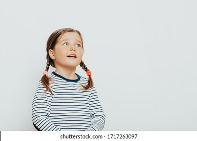 Happy and surprised child girl with excited expression. Cute girl 4-5 year old posing in studio.