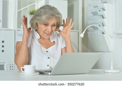 happy surprised Elderly woman working on laptop in office