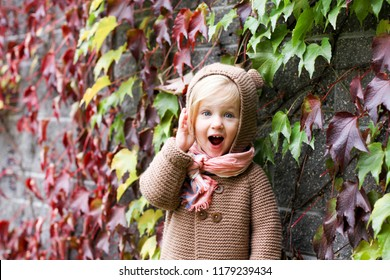 Happy surprised little child, baby girl laughing and playing in the autumn on the nature. Autumn concept, hello autumn.