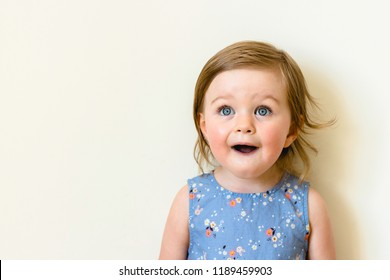 Happy surprised toddler with her mouth open isolated on white. closeup portrait of child girl wearing dress