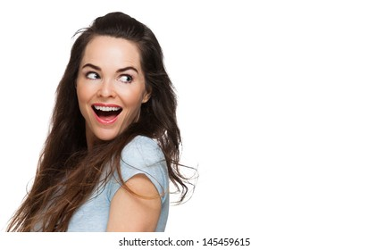 A happy surprised woman looking over her shoulder at copy-space. Isolated on white.
