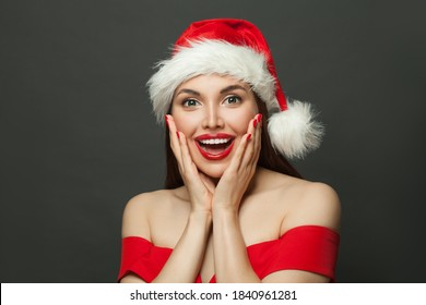 Happy surprised woman in Santa hat on black background. Christmas holiday and New Year party concept