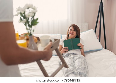 Happy and surprised young woman lying in bed in the morning while her husband is bringing her breakfast and flowers on a tray