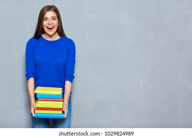 Happy surprising girl holding books stack. Blue casual clothes dressed.