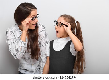 Happy surprising mother and excite kid in fashion glasses looking each other with opened mouth on empty copy space background.
