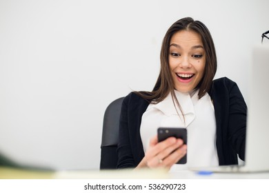 Happy surprising woman looking in mobile phone and reading message with open mouth