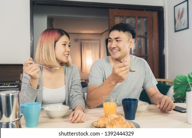 Happy sweet Asian couple having breakfast, cereal in milk, bread and drinking orange juice after wake up in the morning. Husband and his wife eating food together.