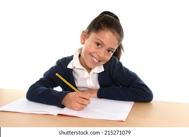 Happy sweet little hispanic female child writing homework with pencil smiling in children education and back to school concept isolated on white background