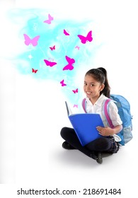 Happy sweet little Hispanic school girl smiling reading magic book with wonderful stories and tales represented by pink  butterflies flying out the pages in children imagination concept