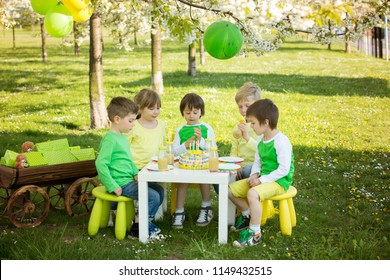 Happy sweet preschool children, friends and relatives, celebrating fifth birthday of cute boy, outdoor in blooming apple tree garden, springtime, late afternoon