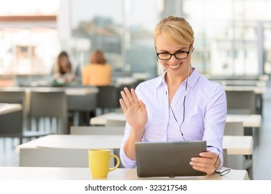 Happy to talk. Delighted upbeat  attractive businesswoman holding laptop and sitting at the table while talking in skype