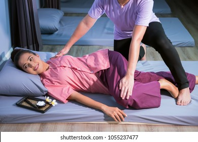 Happy tan beautiful Asian woman having Thai massage on bed with clay cream, wooden stick tool, plumeria flower in spa. Health care and Relax concept.