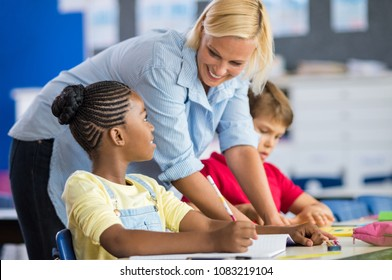 Happy teacher helping her students at elementary school. Teacher help schoolgirl and schoolboy writing test in classroom. Blonde teacher woman helping pupils studying at desk in classroom.