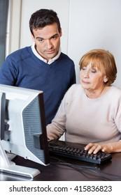 Happy Teacher Helping Senior Woman In Computer Class