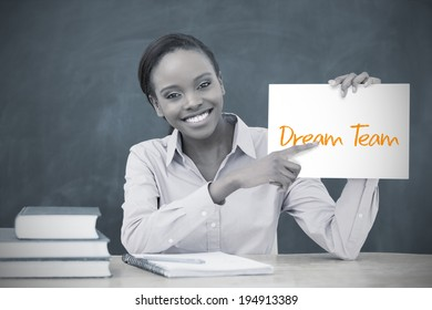 Happy teacher holding page showing dream team in her classroom at school