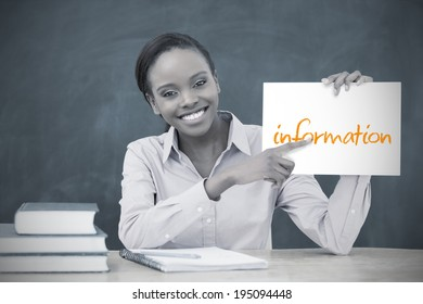 Happy teacher holding page showing information in her classroom at school