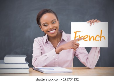 Happy teacher holding page showing french in her classroom at school