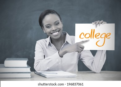 Happy teacher holding page showing college in her classroom at school