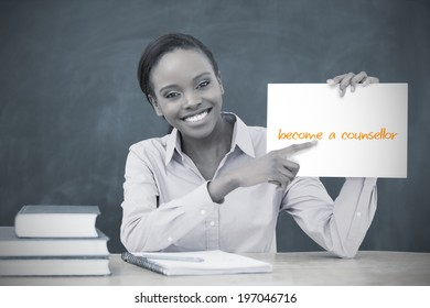 Happy teacher holding page showing become a counsellor in her classroom at school