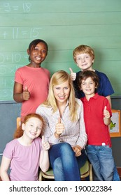 Happy teacher and students holding thumbs up in elementary school